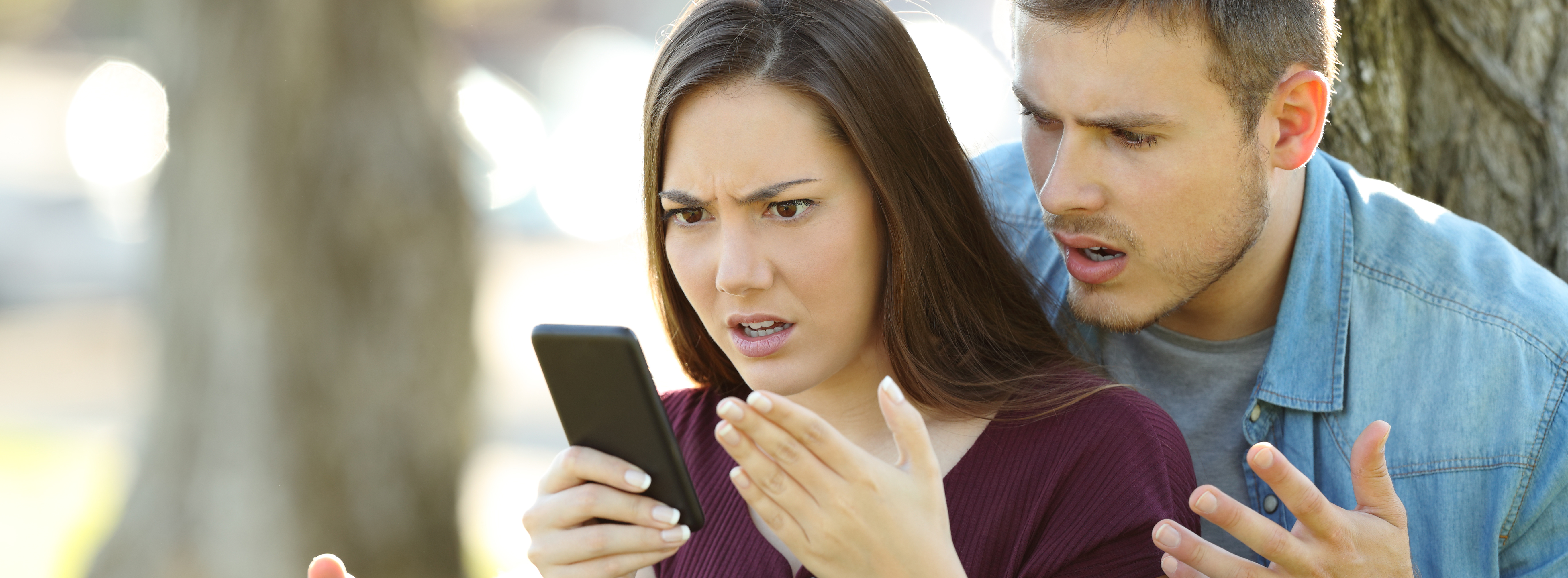 Angry couple using a smart phone outdoors sitting in a park